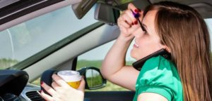 Distracted female driver applying makeup