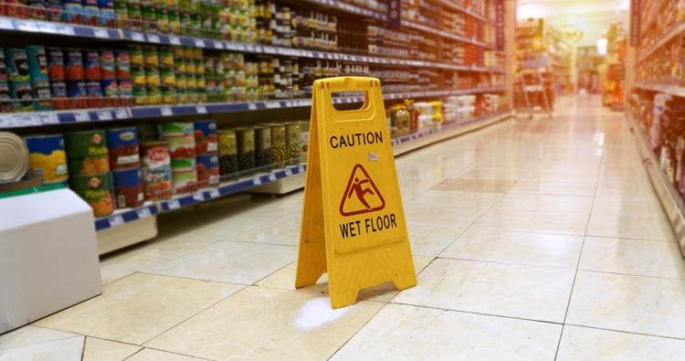 A wet floor sign in a New York store warning customers about hazardous conditions.