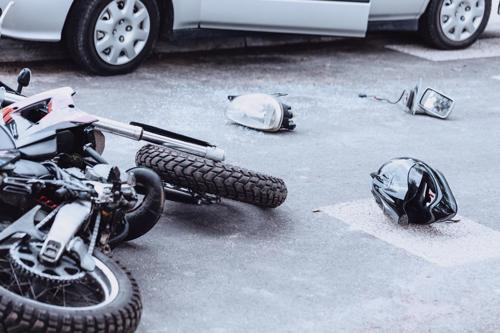 A motorcycle, helmet, and parts of a car lying on a road after an accident.