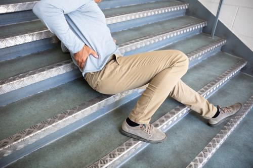 A man holding his lower back after slipping on a staircase.
