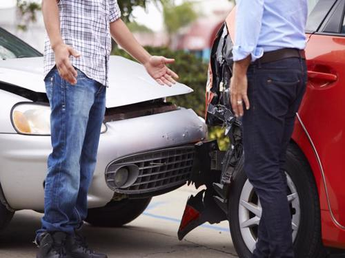 Two drivers exchanging information after a rear-end accident. Contact a Bronx Uber accident lawyer at Cellino Law.