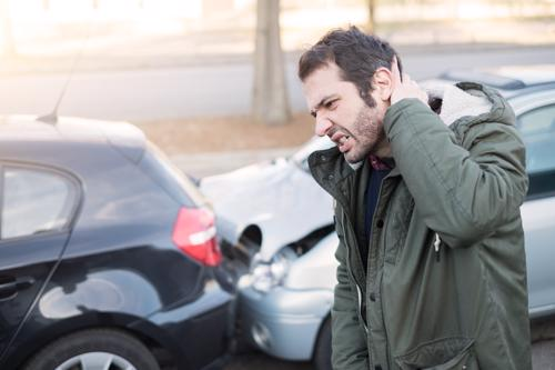 A man holding his neck in pain after being in a rear-end car accident.