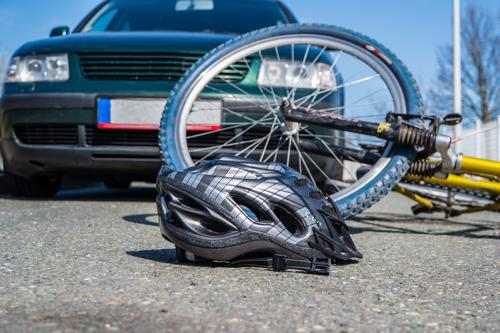 A helmet and bicycle lying on the pavement in front of a car after an accident.