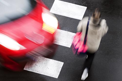 A car speeding towards a woman walking on a crosswalk.