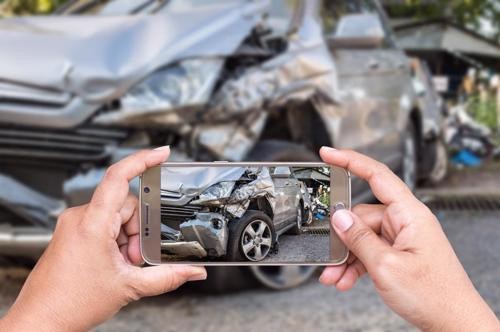 A person taking photos of the damage their car sustained in an accident.