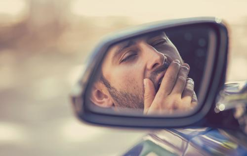 A man showing signs of fatigue while driving.