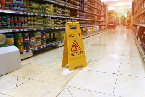 A wet floor and warning sign on a supermarket floor.