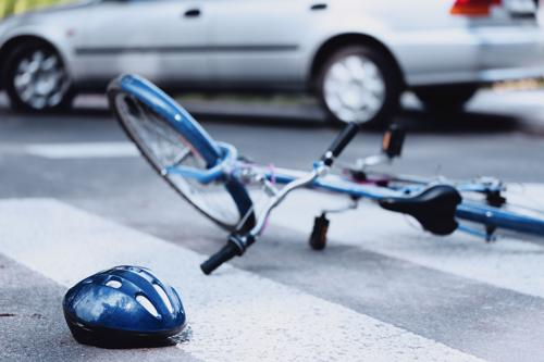 A bicycle and helmet lying on a road after an accident with a car.