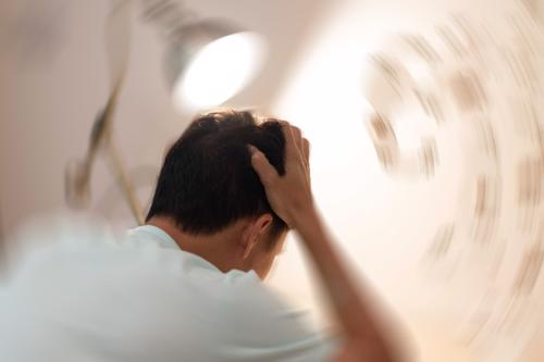 A stylized photo of a man in a room with a blurry background to imply difficulty focusing vision after a blow to the head.