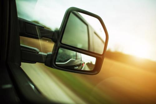 A close up photo of a rear-view mirror on a tractor-trailer.