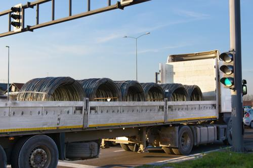 A truck transporting several large spools of wire which can cause a serious accident if not properly secured.