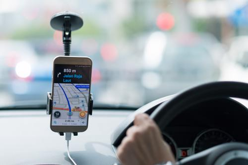 A driver using the Uber app to drive a client to their destination.