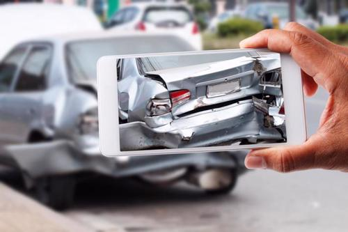 A person taking a photo of damage to a car after an accident.