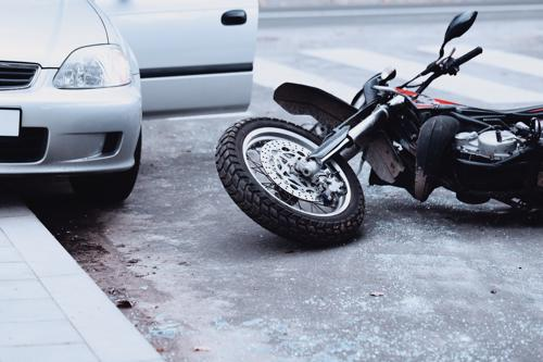 A motorcycle lying in the road after an accident was caused by someone carelessly opening their car door.