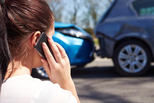 A woman calling a lawyer after a rear end accident with an Uber.