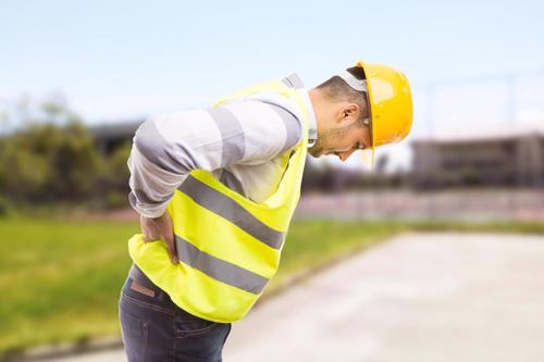 A man in safety equipment holding his lower back after being injured at work.