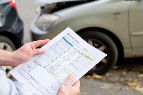 An insurance adjuster reviewing damage to a car after an accident.