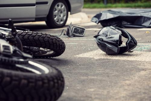 A motorcycle and helmet lying on a road after an accident with a car.