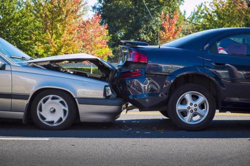 A rear-end car accident between two sedans.