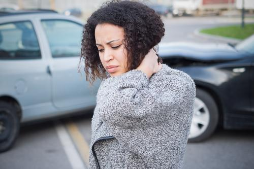 A woman holding her neck after a car accident.