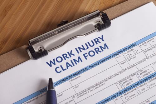 A work injury form and clipboard on a desk.