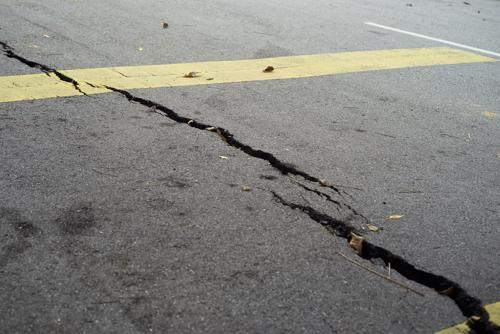 A large crack in a road, an issue that can lead to a motorcycle accident.