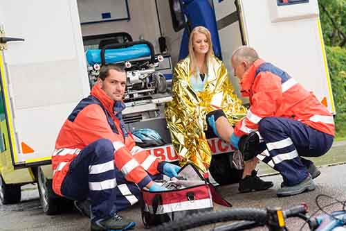 This image shows a woman being treated in an ambulance after a bicycle crash.