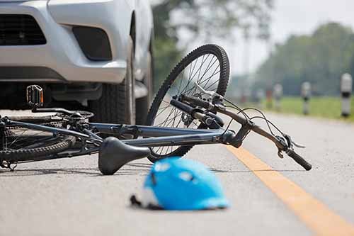 This image shows a bicycle and helmet on the road near a car. If you need a Garden City bicycle accident lawyer, call Cellino Law.
