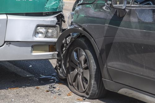 A sedan with fender and tire damage after a bus accident.