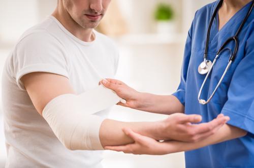 A man having an elbow sprain treated by a medical professional.