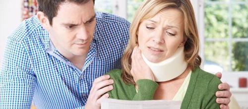 A woman with a neck injury looking at a settlement offer from an insurance company.