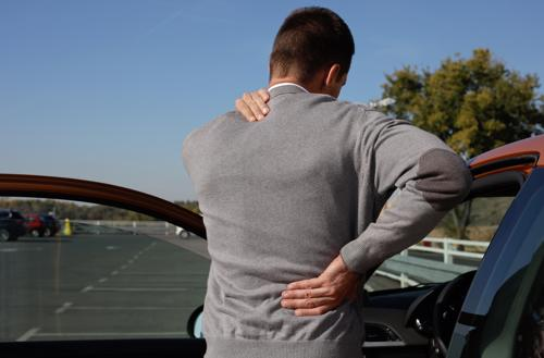 A man holding his back in pain after a car accident.