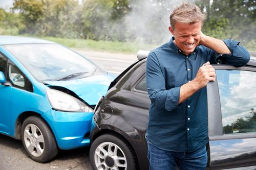 A man holding his neck while getting out of a car after a rear-end accident.