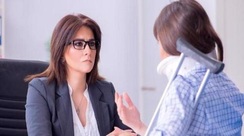 A woman meeting with an attorney to file an injury claim.