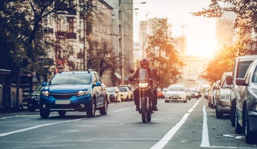 A photo of a man riding a motorcycle in a city.