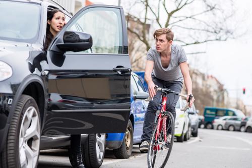 A cyclist narrowly avoiding colliding with an open car door.