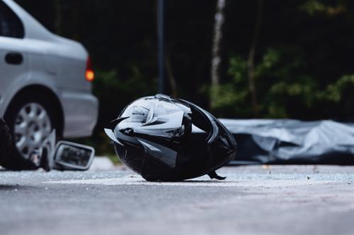 A motorcycle helmet lying in a road and a car in the background after an accident.