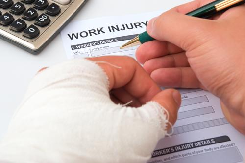 A person with a bandaged hand filling out a work injury form.