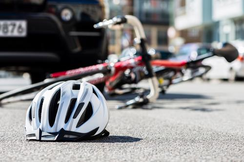 A bicycle and helmet lying in a street after an accident with a car.