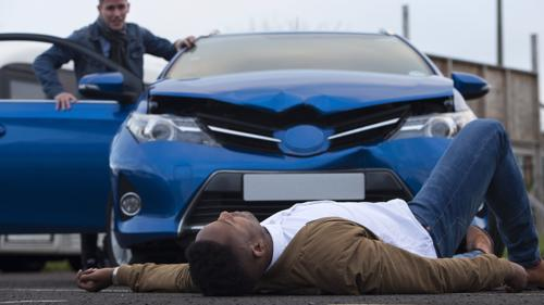 A man lying in the road after being hit by a car.