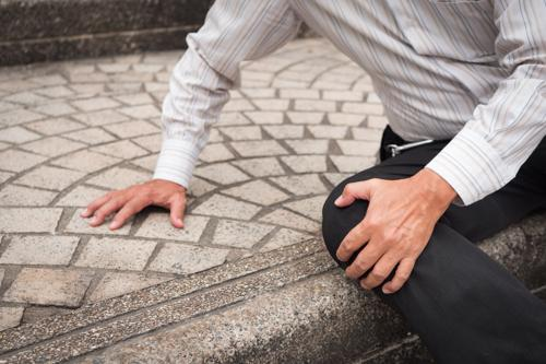 A man with a knee injury after falling on a poorly maintained staircase.