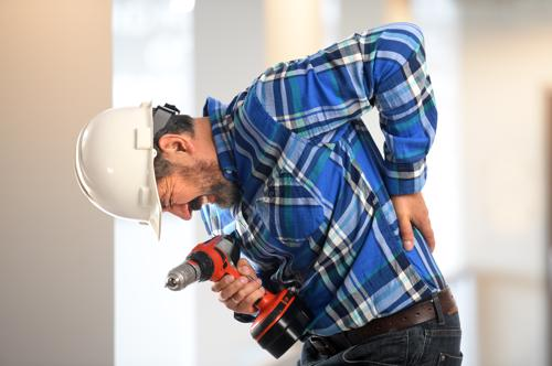A construction worker holding his injured lower back.