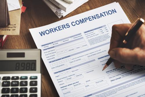 A person filing out a workers compensation form.