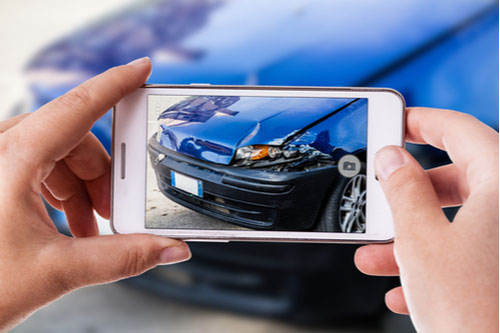 woman using a smartphone to take picture of car damaged in crash