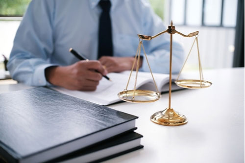 Irondequoit slip and fall lawyer at desk with scales of justice