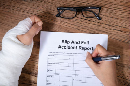 Woman with fractured hand filling out slip and fall injury report